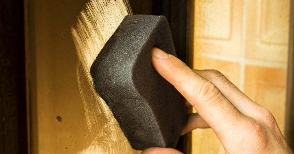 Cleaning a glass pane with steel wool